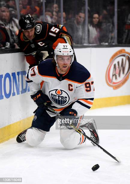 Connor McDavid of the Edmonton Oilers watches the puck from his knees in front of Ryan Getzlaf of the Anaheim Ducks during the second period at Honda...