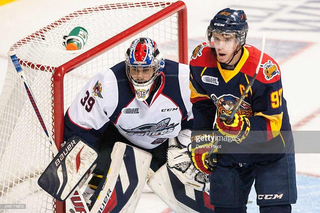Connor McDavid #97 of the Erie Otters battles for the puck in front of the net against Alex Fotinos #39 of the Windsor Spitfires on September 26, 2014 at the WFCU Centre in Windsor, Ontario, Canada.