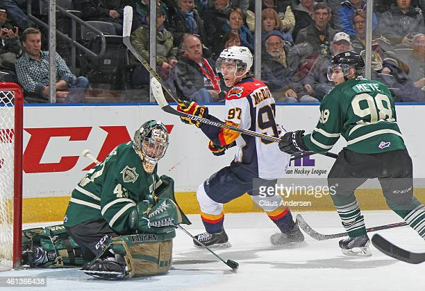 Connor McDavid of the Erie Otters flips a puck between Michael Giugovaz and Victor Mete of the London Knights in an OHL game at Budweiser Gardens on...