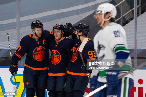 Connor McDavid, Tyson Barrie and Ryan Nugent-Hopkins of the Edmonton Oilers celebrate a goal against the Vancouver Canucks at Rogers Place on January...
