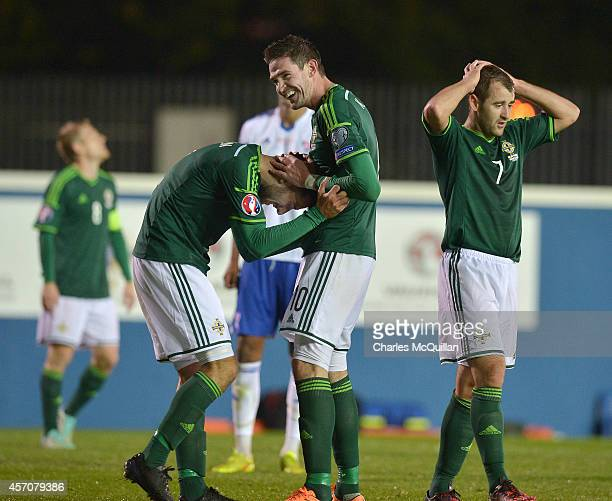 Connor McLaughlin of Northern Ireland is consoled after a bad miss by Kyle Lafferty as Niall McGinn holds his head in his hands during the Euro 2016...