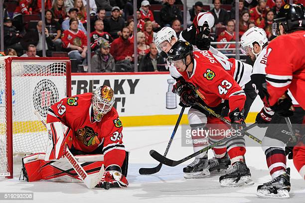 Connor Murphy and Brad Richardson of the Arizona Coyotes swing at the puck against Viktor Svedberg of the Chicago Blackhawks in front of goalie Scott...