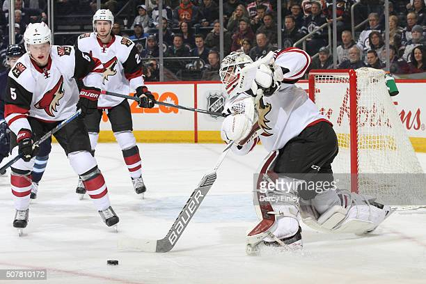 Connor Murphy and Oliver EkmanLarsson of the Arizona Coyotes watch as teammate Louis Domingue plays the puck away from the net during first period...