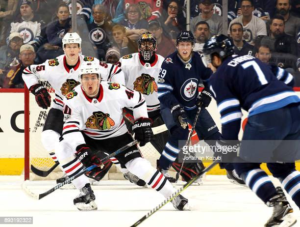 Connor Murphy John Hayden goaltender Corey Crawford of the Chicago Blackhawks and Patrik Laine of the Winnipeg Jets keep an eye on the point during...