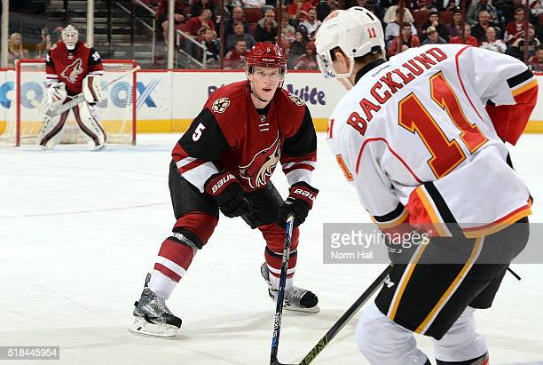 Connor Murphy of the Arizona Coyotes skates back into his own zone while defending Mikael Backlund of the Calgary Flames at Gila River Arena on March...