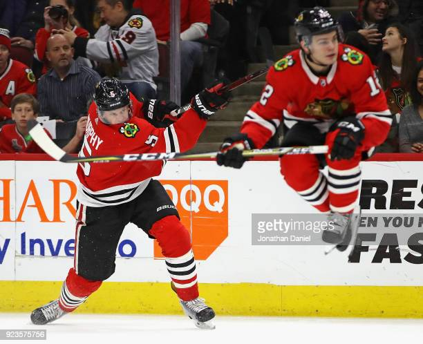 Connor Murphy of the Chicago Blackhawks gets off a shot as Alex DeBrincat leaps out of the way against the San Jose Sharks at the United Center on...