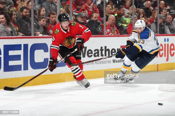Connor Murphy of the Chicago Blackhawks hits the puck past Dmitrij Jaskin of the St Louis Blues in the first period at the United Center on March 18...