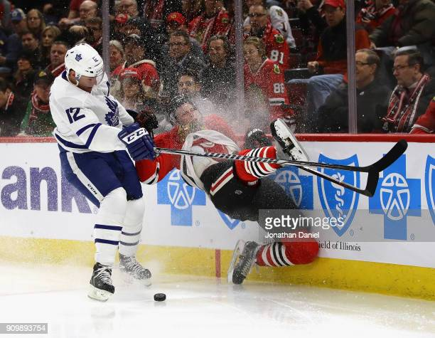 Connor Murphy of the Chicago Blackhawks hits the wall after chasing the puck with Patrick Marleau of the Toronto Maple Leafs at the United Center on...