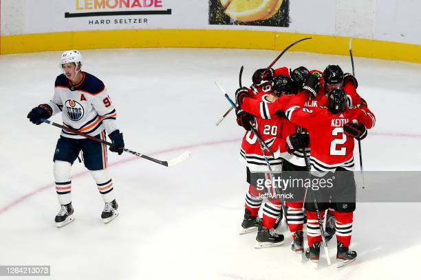 Connor Murphy of the Chicago Blackhawks is congratulated by his teammates after scoring a go-ahead goal as Ryan Nugent-Hopkins of the Edmonton Oilers...