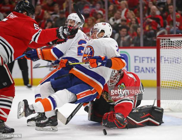 Connor Murphy of the Chicago Blackhawks shoves Jordan Eberle of the New York Islanders into Robin Lehner as Lehner makes a save at the United Center...