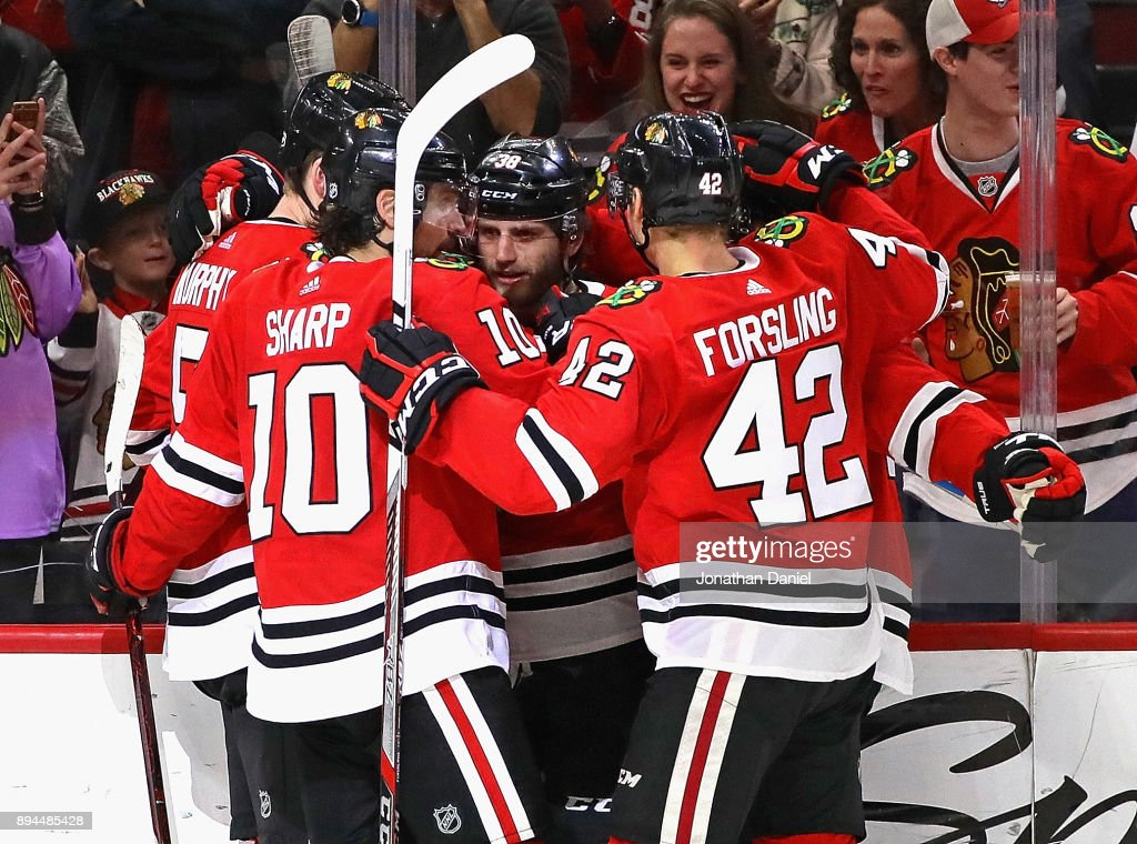 Connor Murphy #5, Patrick Sharp #10 and Gustav Forsling #42 of the Chicago Blackhawks congratulate Ryan Hartman #38 (center) after Hartman scored a third period goal against the Minnesota Wild at the United Center on December 17, 2017 in Chicago, Illinois. The Blackhawks defeated the Wild 4-1.