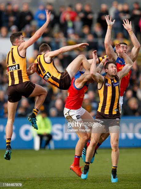 Connor Nash of the Hawks makes a big leap for the ball over Brisbane Lions players during the round 19 AFL match between the Hawthorn Hawks and the...