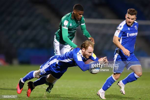 Connor Ogilvie of Gillingham FC is brought down by Timothy Eyoma of Lincoln City as Alex MacDonald of Gillingham FC during the Sky Bet League One...