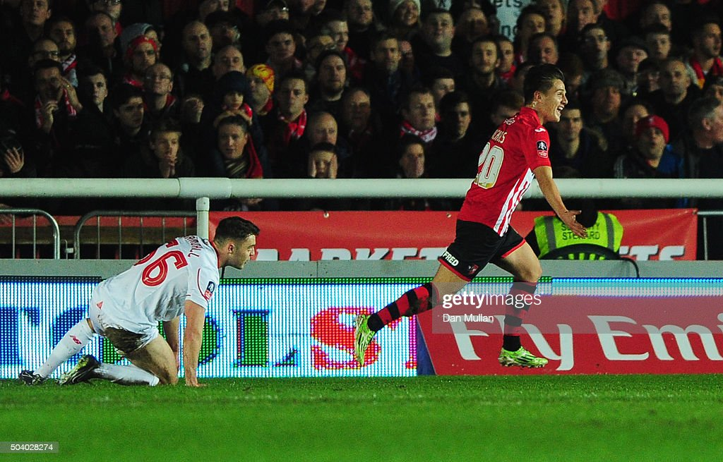 Connor Randall of Liverpool looks dejected as Tom Nichols of Exeter City celebrates scoring their opening goal during the Emirates FA Cup third round match between Exeter City and Liverpool at St James Park on January 8, 2016 in Exeter, England.