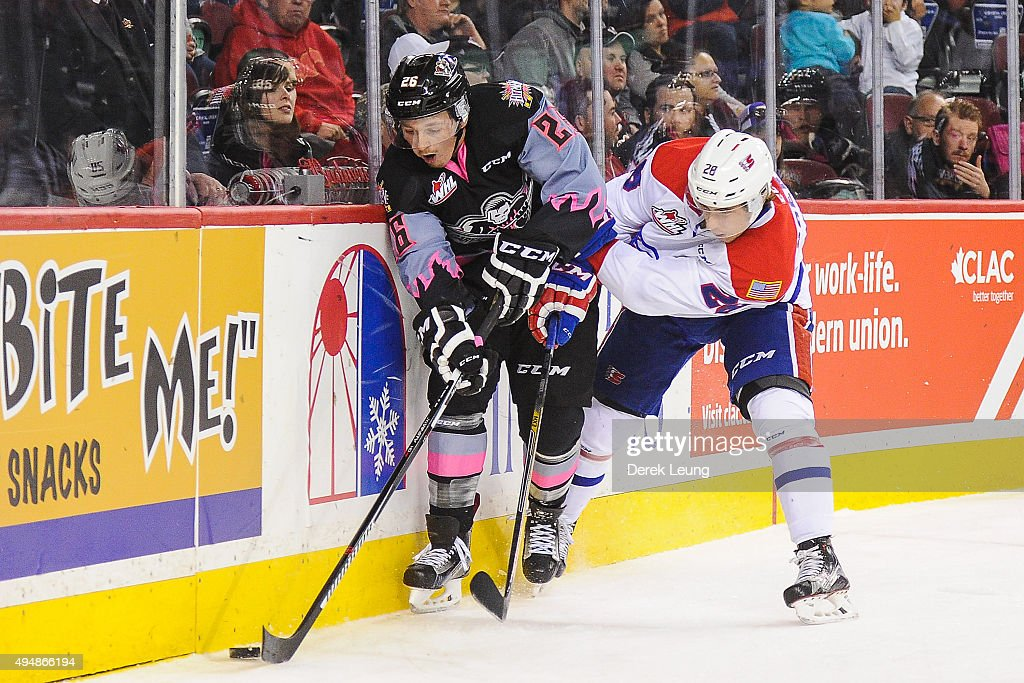 Connor Rankin #26 of the Calgary Hitmen battles for the puck against Nik Andersen #28 of the Spokane Chiefs during a WHL game at Scotiabank Saddledome on October 29, 2015 in Calgary, Alberta, Canada.