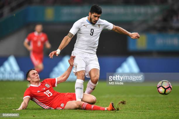 Connor Roberts left of Wales national football team challenges Luis Suarez of Uruguay national football team in their final match during the 2018...