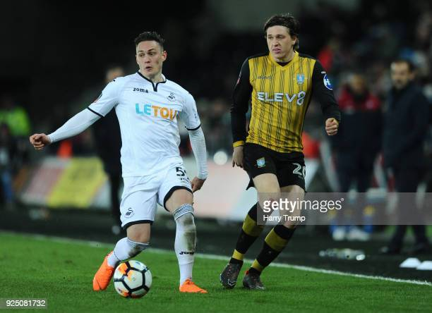 Connor Roberts of Swansea breaks past Adam Reach of Sheffield Wednesday during the Emirates FA Cup Fifth Round Replay match between Swansea City and...