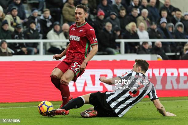 Connor Roberts of Swansea City challenged by Paul Dummett of Newcastle during the Premier League match between Newcastle United and Swansea City at...