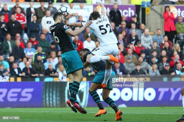 Connor Roberts of Swansea City is challenged by Wesley Hoedt of Southampton during the Premier League match between Swansea City and Southampton at...
