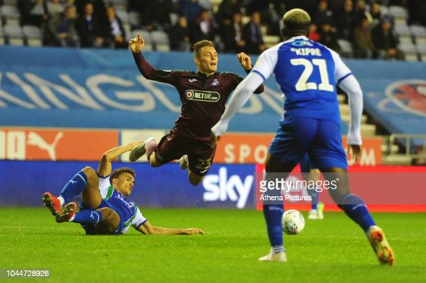 Connor Roberts of Swansea City is tackled by Antonee Robinson of Wigan Athletic during the Sky Bet Championship match between Wigan Athletic and...