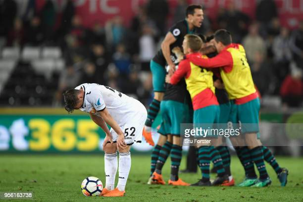 Connor Roberts of Swansea City looks dejected as Southampton celebrate victory during the Premier League match between Swansea City and Southampton...