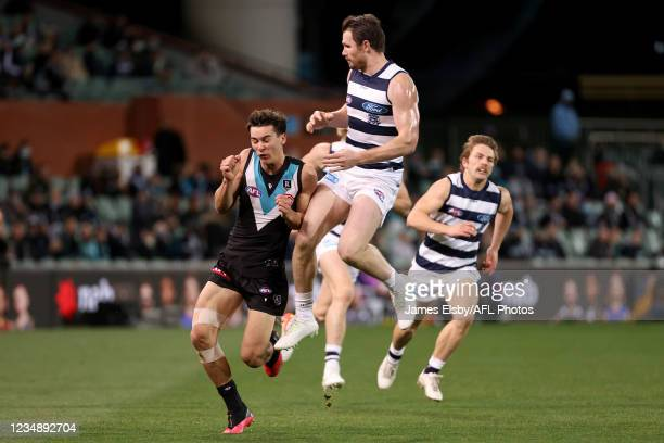 Connor Rozee of the Power clashes with Patrick Dangerfield of the Cats during the 2021 AFL Round 23 match between the Adelaide Crows and the North...
