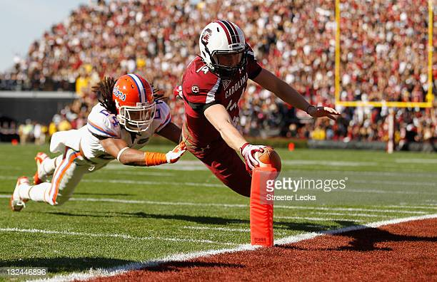 Connor Shaw of the South Carolina Gamecocks dives for a touchdown as Josh Evans of the Florida Gators tries to make a tackle during their game at...