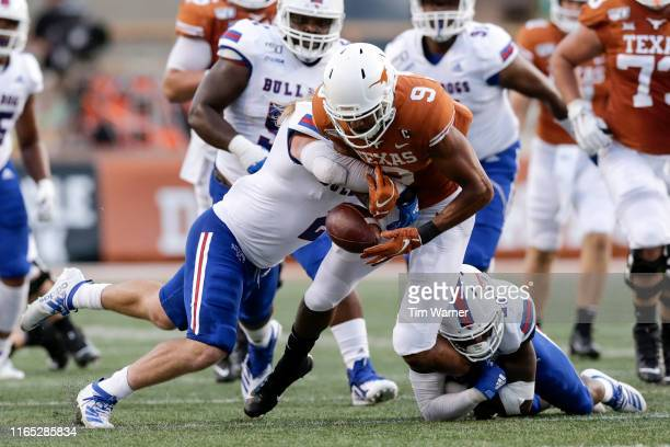 Connor Taylor of the Louisiana Tech Bulldogs hits Collin Johnson of the Texas Longhorns forcing a fumble in the first quarter at Darrell K RoyalTexas...