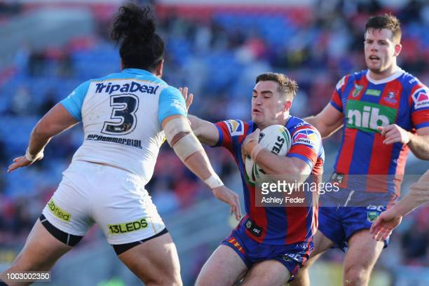 Connor Watson of the Knights is tackled by the Titans defence during the round 19 NRL match between the Newcastle Knights and the Gold Coast Titans...