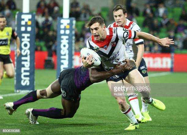 Connor Watson of the Roosters is challenged by Suliasi Vunivalu of the Storm during the round 23 NRL match between the Melbourne Storm and the Sydney...