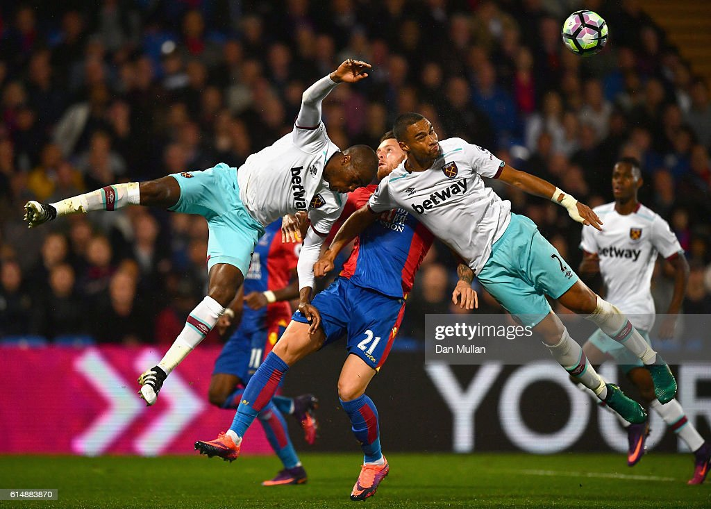 Connor Wickham of Crystal Palace battles with Angelo Ogbonna and Winston Reid of West Ham United during the Premier League match between Crystal Palace and West Ham United at Selhurst Park on October 15, 2016 in London, England.
