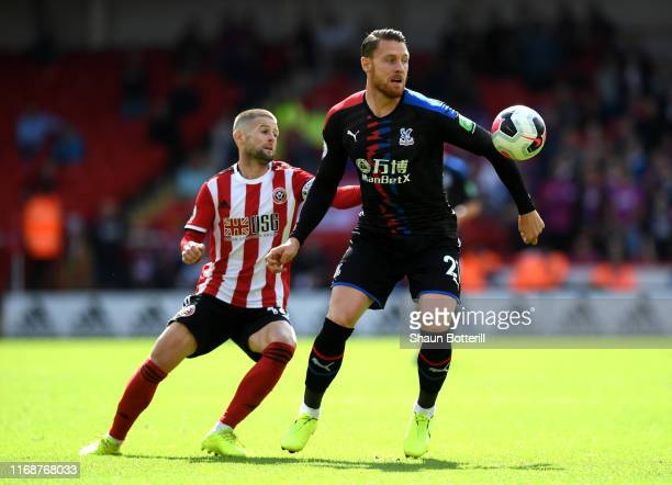 Connor Wickham of Crystal Palace is challenged by Oliver Norwood of Sheffield Unitedduring the Premier League match between Sheffield United and...