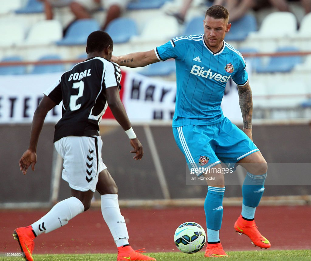 Connor Wickham of Sunderland (R) takes on Zinadine of CD National during a pre-season friendly match between CD National and Sunderland at the Estadio Municipal Albufeira on July 30, 2014 in Albufeira, Portugal.