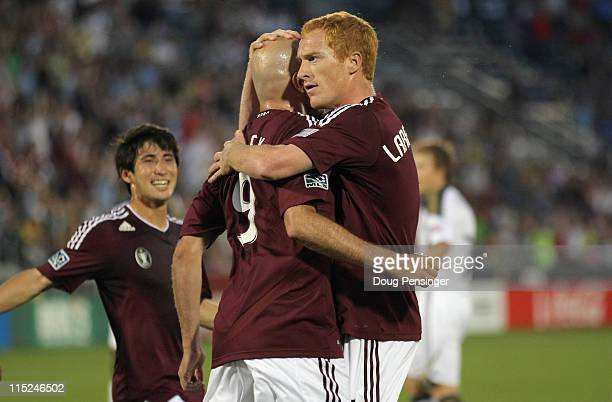 Conor Casey of the Colorado Rapids celebrates his goal with Jeff Larentowicz and Kosuke Kimura of the Rapids on a penalty shot against the...