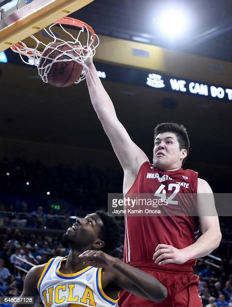 Conor Clifford of the Washington State Cougars dunks over Isaac Hamilton of the UCLA Bruinsin the first half of the game at Pauley Pavilion on March...