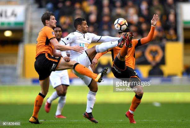 Conor Coady and Helder Costa of Wolverhampton Wanderers tackle Wayne Routledge of Swansea City during the The Emirates FA Cup Third Round match...