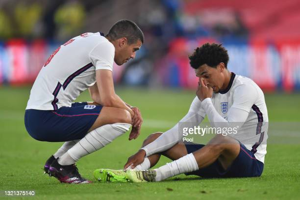 Conor Coady of England interacts with team mate Trent Alexander-Arnold after picking up an injury during the international friendly match between...