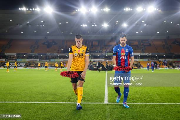 Conor Coady of Wolverhampton Wanderers and Luka Milivojevic of Crystal Palace lay a poppy wreath in honour of Remembrance Day during the Premier...