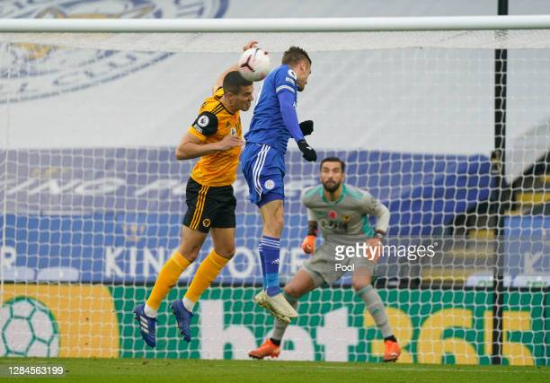 Conor Coady of Wolverhampton Wanderers battles for possession with Jamie Vardy of Leicester City during the Premier League match between Leicester...