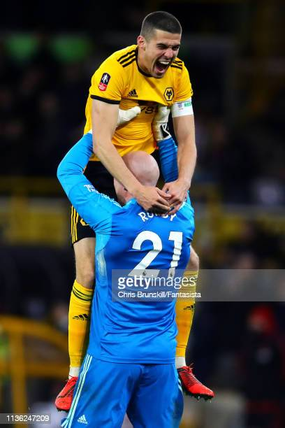 Conor Coady of Wolverhampton Wanderers celebrates with teammate John Ruddy at fulltime following the FA Cup Quarter Final match between Wolverhampton...
