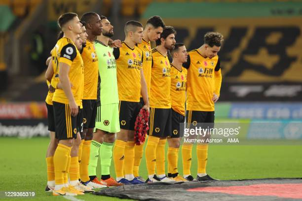 Conor Coady of Wolverhampton Wanderers holds a branded poppy wreath for Remembrance Day during the Premier League match between Wolverhampton...