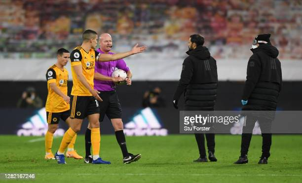 Conor Coady of Wolverhampton Wanderers interacts with Match Referee Lee Mason during the Premier League match between Wolverhampton Wanderers and...
