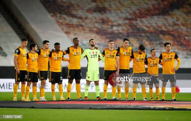 Conor Coady of Wolverhampton Wanderers is seen holding a Poppy Wreath as Wolverhampton Wanderers players observe a minute of silence whilst the last...
