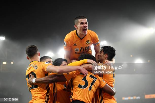 Conor Coady of Wolverhampton Wanderers jumps on his team-mates as they celebrate Raul Jimenez scoring his team's first goal during the Premier League...
