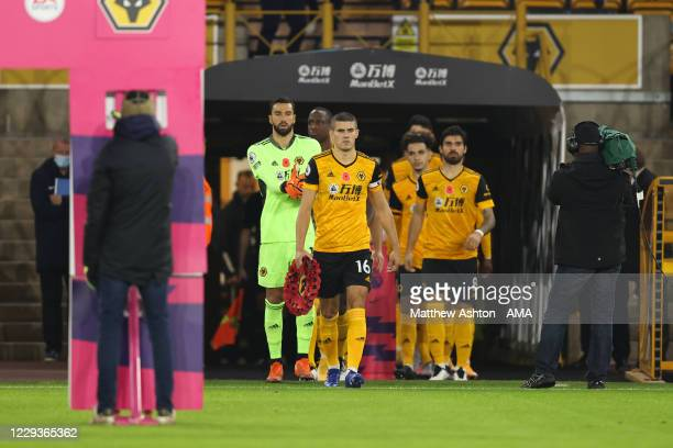 Conor Coady of Wolverhampton Wanderers walks out holding a poppy wreath for Remembrance Day during the Premier League match between Wolverhampton...