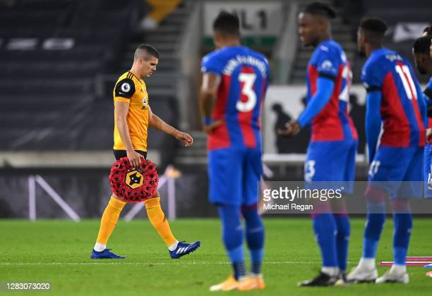 Conor Coady of Wolverhampton Wanderers walks out with a Poppy Wreath ahead of Armistice Day prior to the Premier League match between Wolverhampton...