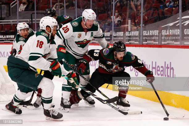 Conor Garland of the Arizona Coyotes attempts to control the puck pressured by Ryan Suter and Jordan Greenway of the Minnesota Wild during the second...