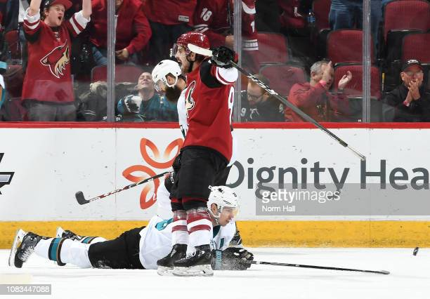 Conor Garland of the Arizona Coyotes celebrates as he skates past Logan Couture and Brent Burns of the San Jose Sharks following a goal by teammate...