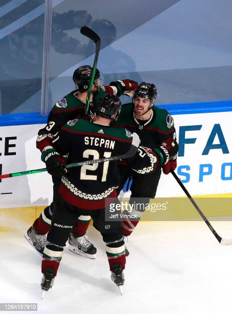 Conor Garland of the Arizona Coyotes celebrates with teammates Oliver Ekman-Larsson and Derek Stepan after Garland scored in the third period against...