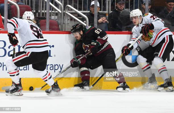 Conor Garland of the Arizona Coyotes plays the puck along the boards between Alex Nylander and Kirby Dach of the Chicago Blackhawks during the first...